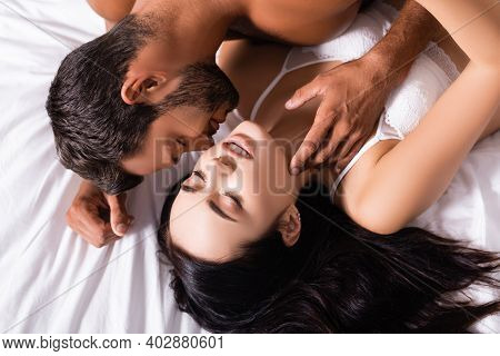 Top View Of Sexy Man Seducing Brunette Woman In Lingerie On Bed