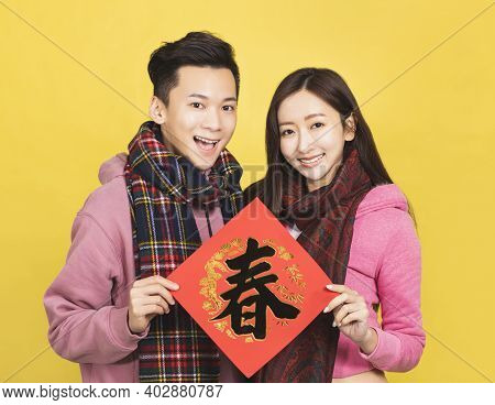 Happy Asian Couple Showing Red Couplets And Celebrating Chinese New Year . Chinese Text: Spring