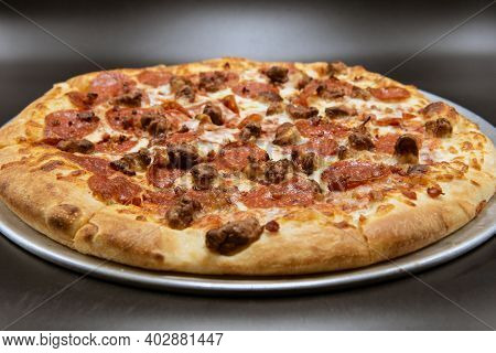 Pepperoni And Sausage Dominate The Top Of The Melted Cheese Pizza Of Meat.