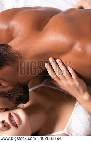 Cropped View Of Muscular Shirtless Man Kissing Woman In Lingerie Indoors