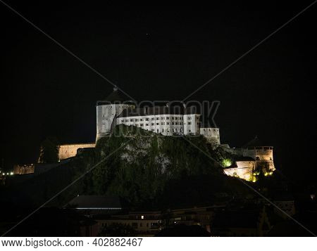 Aerial Panorama Of Illuminated Medieval Castle Festung Kufstein Fortress At Night In Town Tyrol Aust