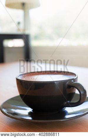 Hot Organic Cocoa With Foam Froth Art In Black Ceramic Cup In Cafe