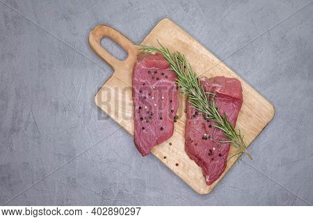 Sliced Beef Steak With Rosemary, Salt And Black Pepper On A Table Prepared For The Grill. Fresh Rib