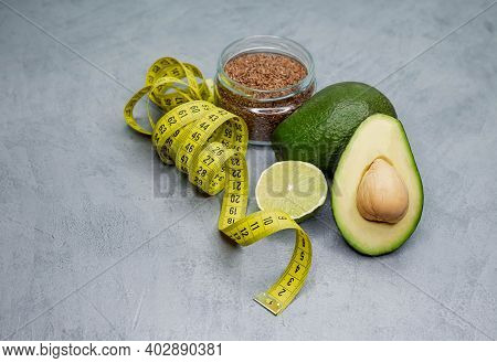 Raw Avocado With Tape Measure On Grey Concrete Background. Healthy Lifestyle, Eating. Proper Nutriti