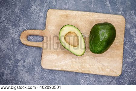 Fresh Avocado Cut In Half On Old Wooden Table. Food Background With Fresh Whole And Sliced Avocado O