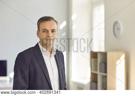 Businessman, Company Executive Manager Or Ceo Looking At Camera Standing In Sunny Office