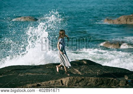A young woman is engaged in choreography on the ocean coast.