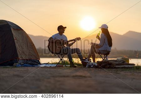 Young adult Asian couple playing guitar and drinking beer beside their tent campsite while sunset. Camping trip with dog outdoor activity campsite concept.