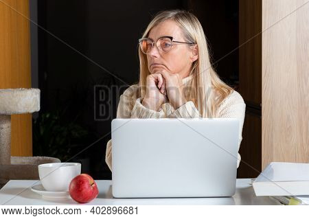 Woman Sitting At Laptop In Home Office And Looking Thoughtfully Into The Distance, Thoughtful Female