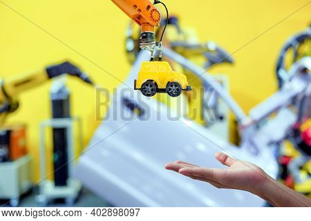 Close-up Industrial Robotic Gripping Yellow Toy Car Send To Hand Human On Blurred Smart Car Factory