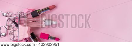 Makeup In Pushcart Isolated On Pink Background.miniature Shopping Trolley Cart With A Set Of Cosmeti