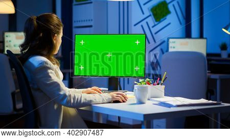 Businesswoman Looking At Green Screen Monitor Of Computer Sitting At Desk In Business Office Late At