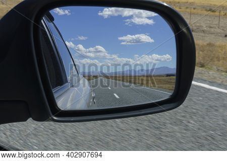 Road And Rural Scenery Behind In Rear-vision Mirror While Traveling Through Rural South Island New Z