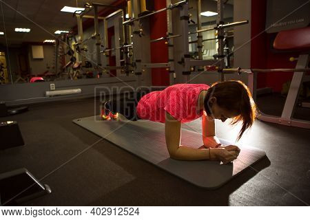 Woman Stands In A Plank In The Gym. Sportswear, Training For The Press And Muscle Strength, Strength