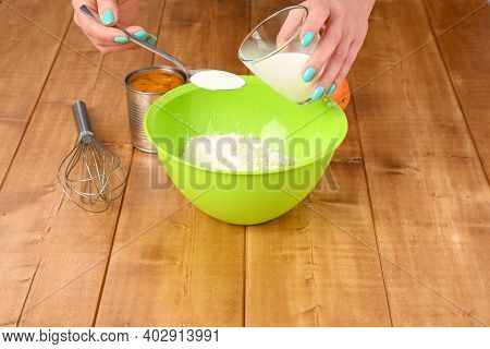 A Woman Pours Milk Into A Tablespoon. Mixing Ingredients For The Pie.