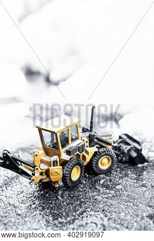 Digger Model Removing Snow After The Storm. Problems Of Adverse Weather Conditions Concept.copy Spac