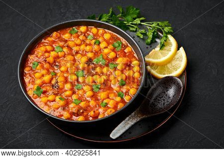 Chana Masala Or Chole In Black Bowl On Dark Slate Table Top. Indian Cuisine Veg Chickpeas Curry Dish