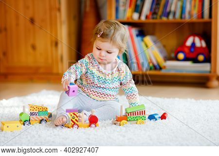 Little Baby Girl Playing With Educational Wooden Toys At Home Or Nursery. Toddler With Colorful Trai
