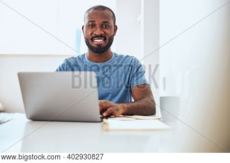 Mixed-race Worker Enjoying His Work On A Laptop