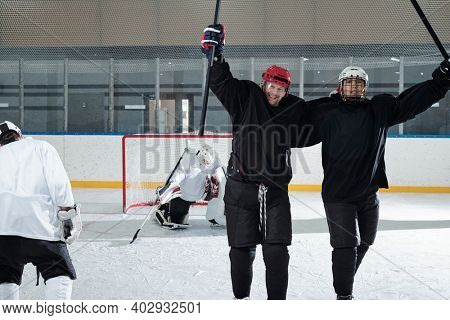 Two excited hockey players in sports uniform, gloves and protective helmets standing in front of camera after play and expressing joy