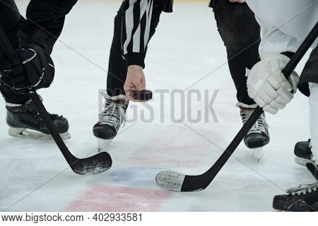 Hand of referee holding puck over ice rink with two hockey players with sticks standing around him and waiting for moment to shoot it