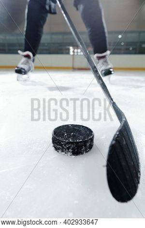 Legs of male hockey player in sports uniform and skates standing on ice rink against stadium environment while going to shoot puck
