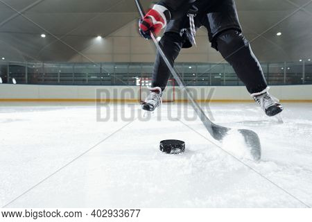 Male hockey player in sports uniform, gloves and skates moving down rink in front of camera against stadium environment while going to shoot puck