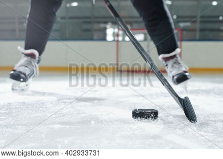 Legs of male hockey player in sports uniform and skates moving down rink in front of camera against stadium environment while going to shoot puck