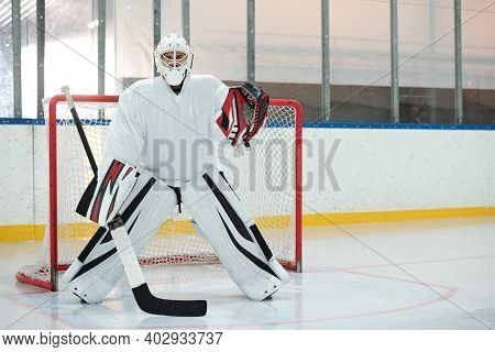 Hockey player in white sports uniform, protective helmet and gloves holding stick while standing on rink against net and waiting for puck