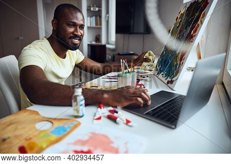Painter Is Tapping On A Laptop Touchpad