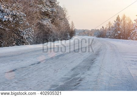 Winter, Icy Road In The Snow. Turning The Road. Trees In Snow And Sunshine. Horizontal Photo. Winter