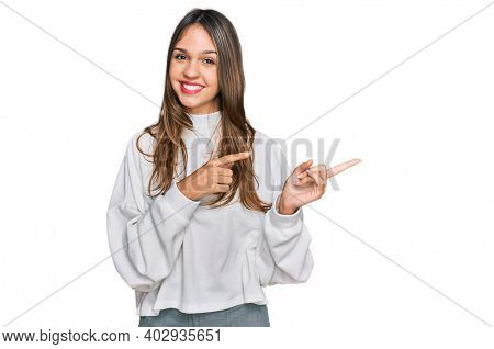 Young brunette woman wearing casual turtleneck sweater smiling and looking at the camera pointing with two hands and fingers to the side.