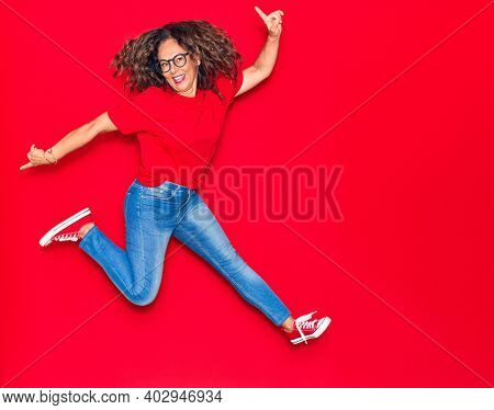 Middle age beautiful hispanic woman wearing casual clothes and glasses smiling happy. Jumping with smile on face over isolated red background