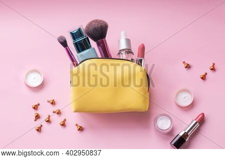 Make Up Bag With Cosmetics And Brushes Isolated On Pink Background. Yellow Bag With Cosmetics.basic