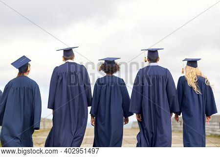 education, graduation and people concept - group of international graduate students in mortar boards and bachelor gowns outdoors