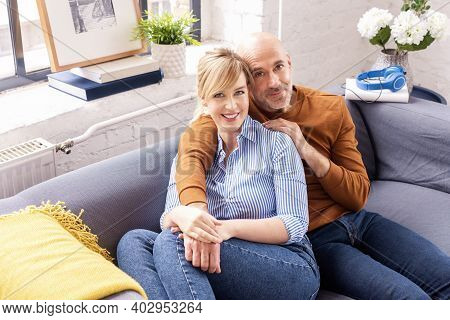 Shot Of Happy Couple Sitting On Couch At Home And Bonding To Each Other While Relaxing At Home.