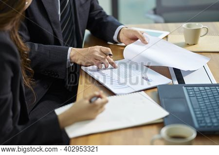 Asian Corporate Executives Working Together Reviewing Business In Office