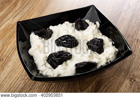 Cottage Cheese With Sour Cream And Prunes In Black Glass Bowl On Brown Wooden Table