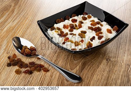 Spoon And Dried Grape, Cottage Cheese With Sour Cream And Raisin In Black Glass Bowl On Brown Wooden