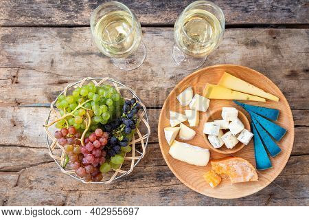 Top View Cheeseboard With Glasses Of Wine And Grapes