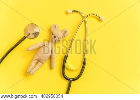 Simply Minimal Design Toy Bear And Medicine Equipment Stethoscope Isolated On Yellow Background. Hea