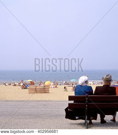 Scheveningen,holland-august 12,2008:people In Old Fashioned Dress Sitting On A Bench At The Boardwal