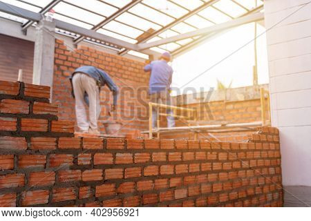 Blurred Image Of Bricklayer Worker Installing Brick Masonry On Exterior Wall With Trowel Putty Knife
