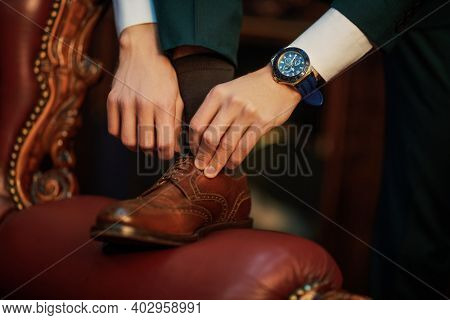 Close-up of a man knotting stylish leather shoes in an expensive vintage interior. Fashionable men's shoes and accessories. Wrist Watch.