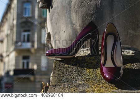 Leather Cherry Womens Shoes On A Stone Wall. Fashion Concept, Womens Shoes, Accessories. Burgundy Wo