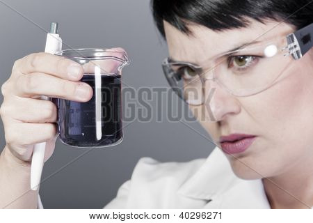 A medical or scientific researcher or doctor looking at a liquid clear solution in a laboratory.