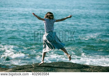 Young dance woman is engaged in choreography on the ocean coast.