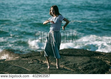 A young dance woman is engaged in choreography on the ocean coast.