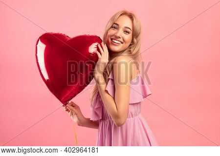 All You Need Is Love. Cheerful Blonde Woman With Red Heart Shaped Balloon Smiling And Looking At Cam