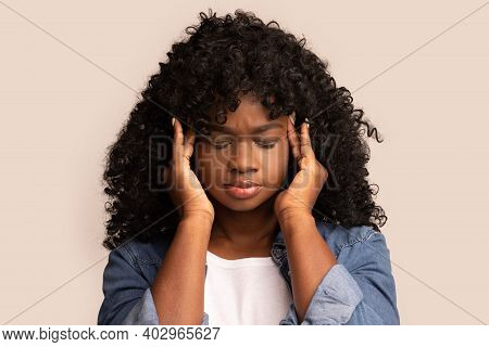 Closeup Of Upset African American Young Lady In Jeans Coat With Curly Hair Having Headache, Touching